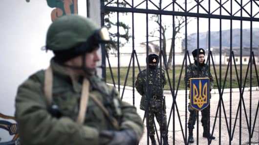 Members of the Russian armed forces stand guard around the Ukrainian military base in the village of Perevalne, 20 km south of Simferopol.